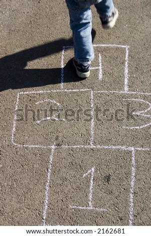 A child is jumping on a hopscotch game in the road.