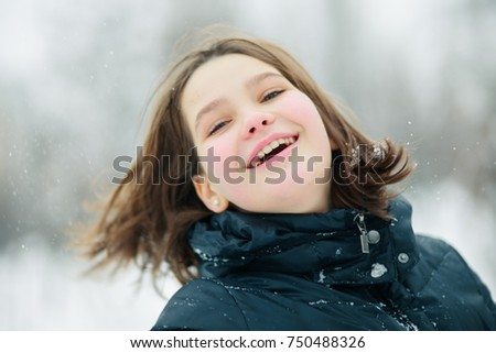A child is smiling happily. The girl opened her mouth with joy. A girl without a hat in a severe frost.