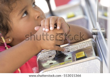 A child looking at screen of arcade machine and holding a joystick. Horizontal outdoors shot