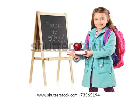 A child next to a school board holding books and red apple isolated on white background