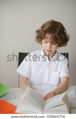 A child of primary school age do homework. The boy does his homework at his desk at home.  - stock photo