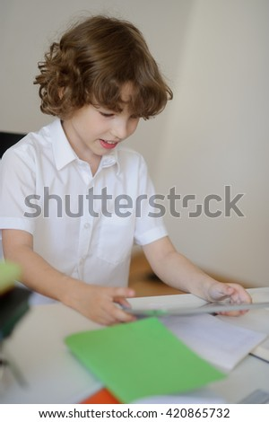 A child of primary school age do homework. The boy does his homework at his desk at home. The child works on a tablet. - stock photo
