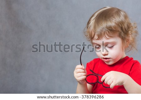 A child of 3 years old  with long hair tries to put on  eye glasses. Gray background  Free space for a text. - stock photo