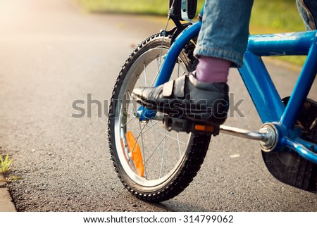 a child on a bicycle in part on asphalt road - stock photo