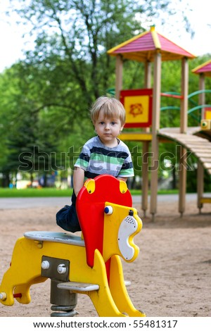 A child on outdoor playground equipment. - stock photo