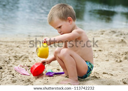 A child playing in the sand on the river bank - stock photo