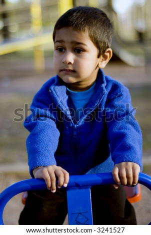A child playing thoughtfully in a local park