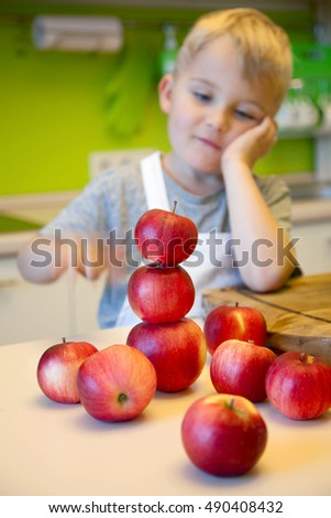 A child playing with apples in the kitchen. Green Kitchen. Boy cook.