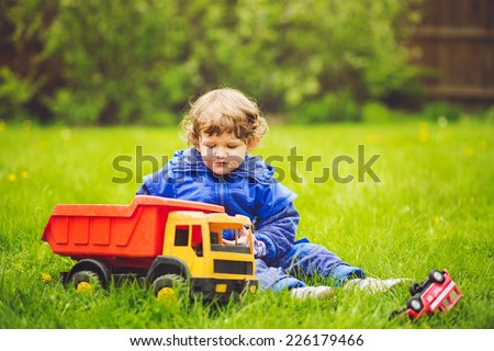 A child plays a toy car on the grass in the park.