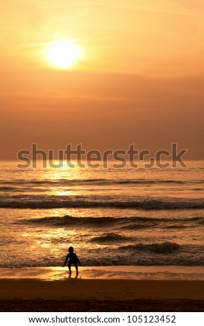 A child plays with the waves on the evening beach - stock photo