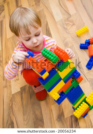 a child plays with toy blocks - stock photo