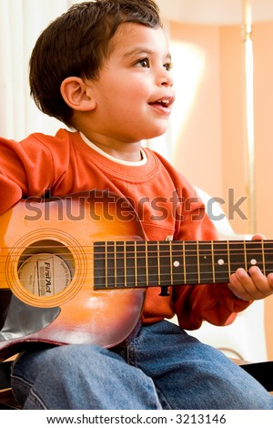 A child practices playing the guitar - stock photo