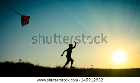 A child running with a kite against the blue sky with the sun - stock photo