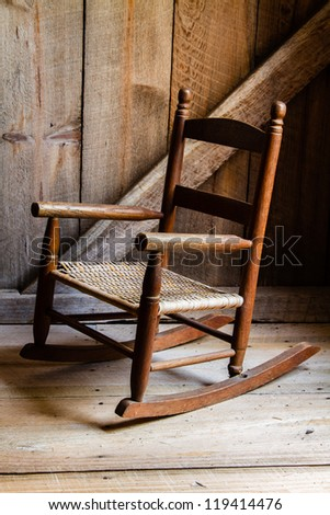 A child's rocking chair waiting to be sat upon. - stock photo