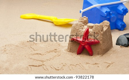 "A child's sandcastle on a beach  with the words "" I heart mummy"" in the foreground and a oof bucket and spade in the background. - stock photo"
