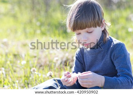 A child sits and thinks. Boy dreaming on grass and sad. - stock photo