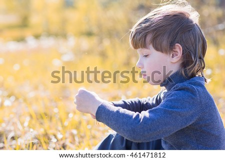 A child sits and thinks. Boy dreaming on grass and sad.