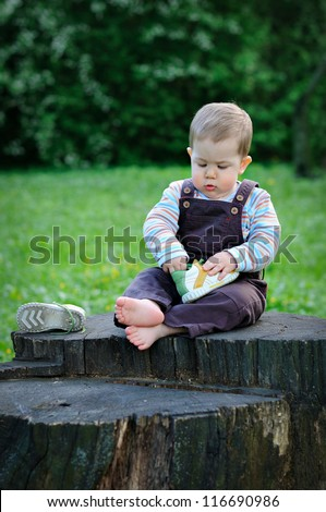 A child sits on a large tree stump with bare feet and playing shoes. Sunny summer day - stock photo