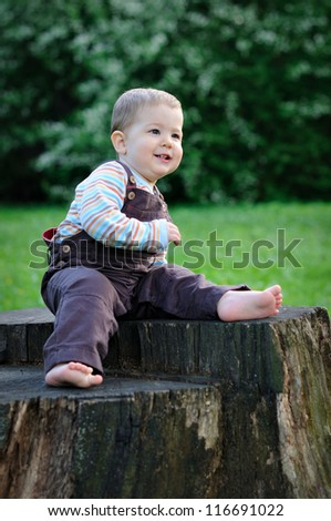 A child sits on a large tree stump with bare feet. Sunny summer day