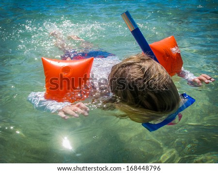 A Child Snorkelling In A Tropical Ocean - stock photo