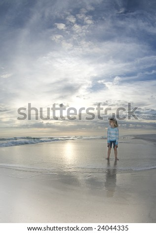 A child watches the surf flow in while the setting sun reflects off the water and the clouds glow on the horizon