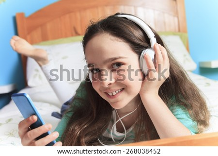 A children girl listening music lay on his bed - stock photo