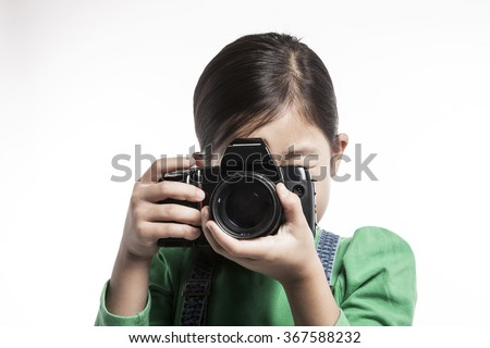 A children girl(woman, female) hold a black camera push shutter button isolated white at the studio. - stock photo