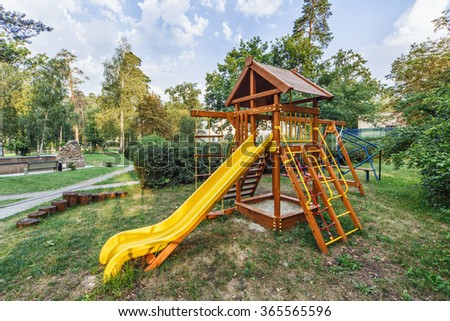 a children's playground in the park with a slide.