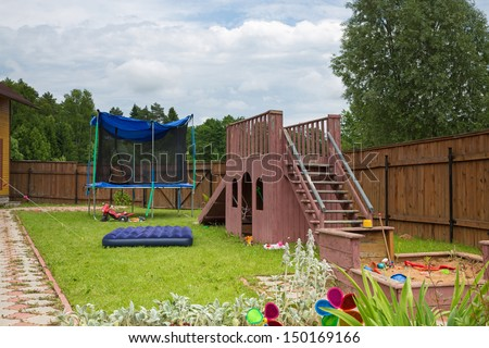A children slide, trampoline and sandbox on the playground in the country house - stock photo