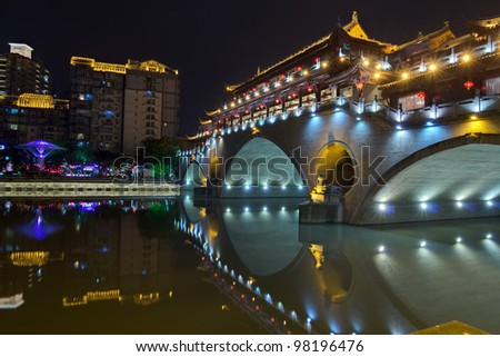 A chinese arch bridge ablaze with lights. - stock photo
