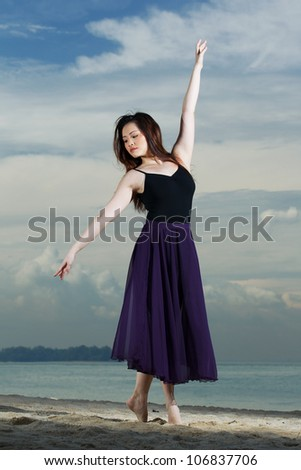 A Chinese beautiful ballerina dancing on the beach.