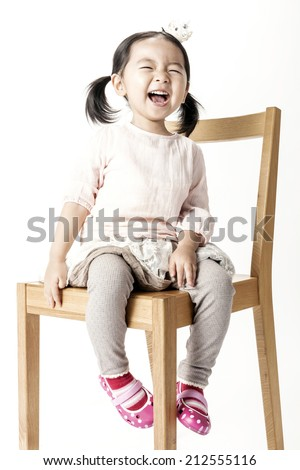 A chinese girl seating wood chair with big smile. - stock photo