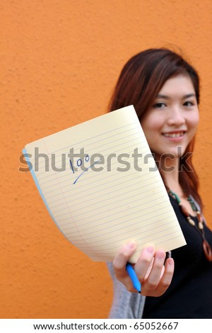 A Chinese girl shows full mark on sheet - stock photo