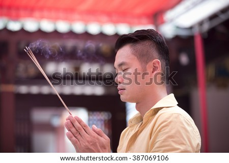 A Chinese man is praying outside a Buddhist temple and burning incense. Asian man praying in a temple.