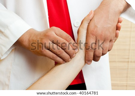 A Chinese medical doctor takes the pulse of a patient - stock photo