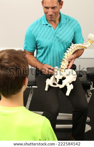 A Chiropractor showing a model of the human spine to a boy