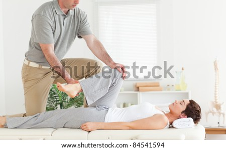A chiropractor stretches woman's arm in his surgery - stock photo