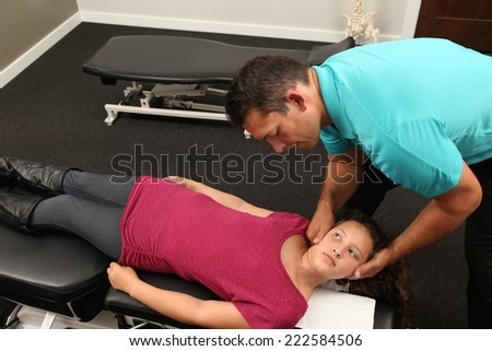 A Chiropractor treating a young girl - stock photo