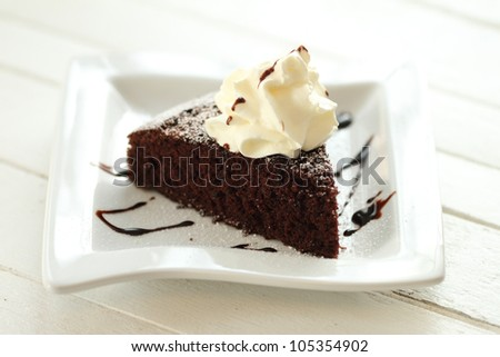 a chocolate cake on white plate with whipping cream