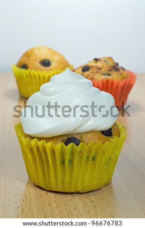 A chocolate chip muffin with fresh cream on top - stock photo