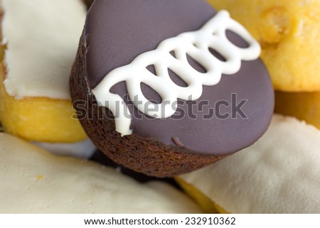 A chocolate frosted and vanilla iced snack cake atop more junk food. - stock photo