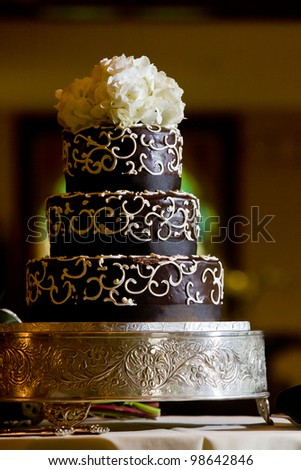 A chocolate wedding cake with white frosting details and flowers on top - stock photo