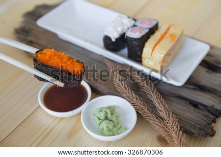 a Chopsticks holding sushi top on sauce  and wasabi, Japanese food - stock photo