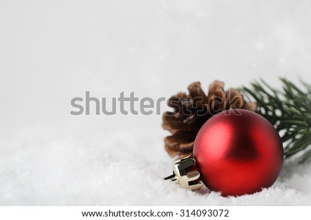 A Christmas border and background with red bauble, fir cone and green branch, nestling in white fake snow in lower right corner.  Twinkling stars in background above. - stock photo