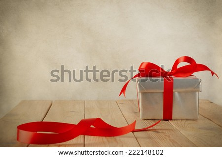 A Christmas gift box wrapped in silver paper and tied to a bow with a red satin ribbon, on a weathered old wooden table with copy space behind and above. Cut ribbon remnant to the side. Vintage style. - stock photo