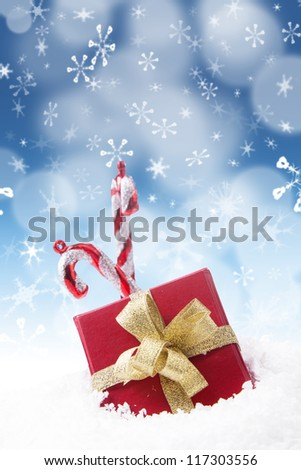 A Christmas gift with two candy sticks on blue defocused lights background - stock photo