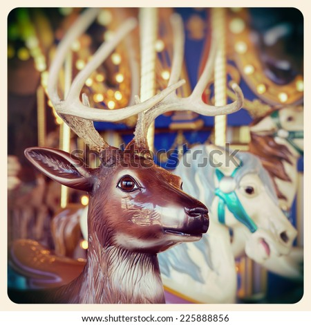 A Christmas reindeer on a carousel ride. Processed  and filtered to look like an aged instant photo. - stock photo