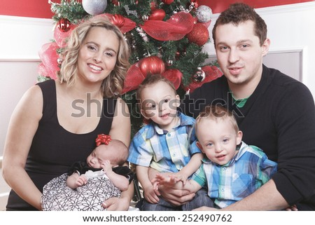 A christmas toddler with his family in front of a fir - stock photo