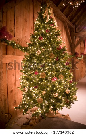 A Christmas tree and pine garland with ribbon and ornaments. - stock photo