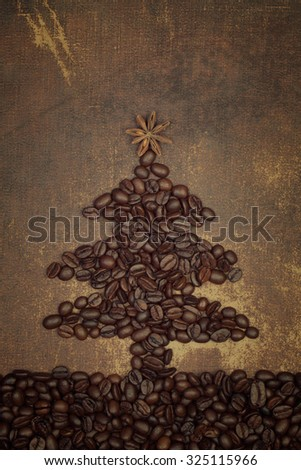 A christmas tree  made out of  roasted coffee beans with a star anise spice on top on shabby chic surface - stock photo
